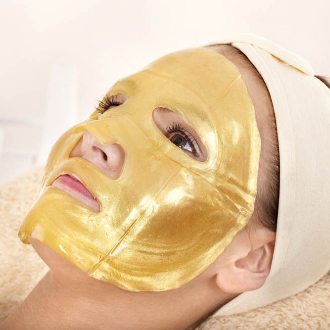 Young womanl with gold facial mask.